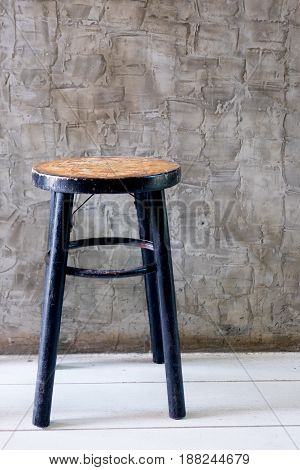 Stool wooden vintage chair with polished walls background in loft style