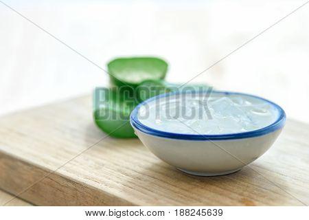 Aloe vera gel on bowl with fresh aloe vera leaves on wooden