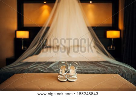 silver Bride shoes on a bed before ceremony. wedding concept