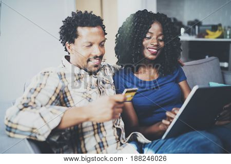 Happy young african american couple shopping online through touch tablet using credit card at home. Horizontal, blurred background