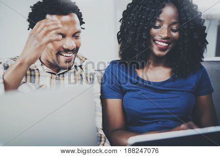 Smiling attractive african american couple using mobile gadgets at home while sitting on the sofa. Horizontal, blurred background