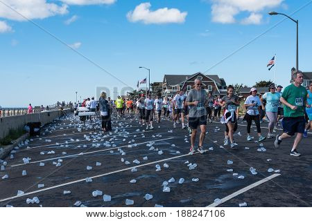 Spring Lake NJ USA -- May 27 2017 Runners in the annual Spring Lake 5 pass discarded cups of water on Ocean Avenue. Editorial Use Only.