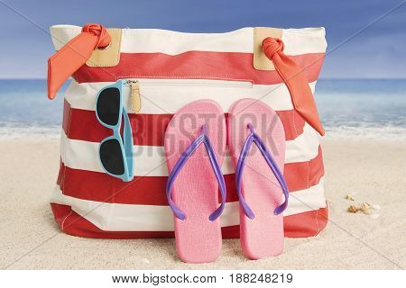 Close up of woman bag with pink sandal and sun glasses on the sandy beach
