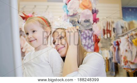 A young mother with a young daughter trying on headbands in front of the mirror in the children's clothing store