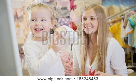 Mother and daughter having fun in front of the mirror in the children's clothing store