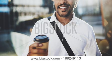 Attractive young American African man in headphone walking at sunny city with take away coffee and enjoying to listen to music on his smartphone.Blurred background.Horizontal wide, Cropped