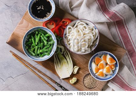 Ingredients for cooking stir fry udon noodles, green beans, sliced paprika, boiled eggs, soy sauce with sesame seeds in traditional bowls with wooden chopsticks over gray texture background. Flat lay