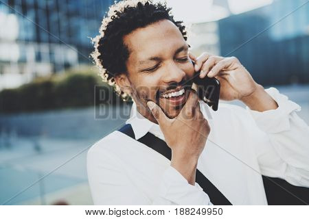 Closeup portrait of happy American African man using smartphone to call friends at sunny street.Concept of happy young handsome people enjoying gadgets outdoors.Blurred background