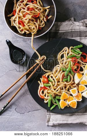 Cooking stir fry udon noodles, green beans, sliced paprika, boiled eggs, soy sauce with sesame seeds in black plate with wood chopsticks over gray texture background. Flat lay. Asian style dinner