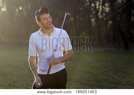 Playful golfer is playing outdoors on playing field.