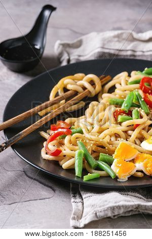 Cooking stir fry udon noodles, green beans, sliced paprika, boiled eggs, soy sauce with sesame seeds in black plate with wood chopsticks over gray texture background. Asian style dinner close up