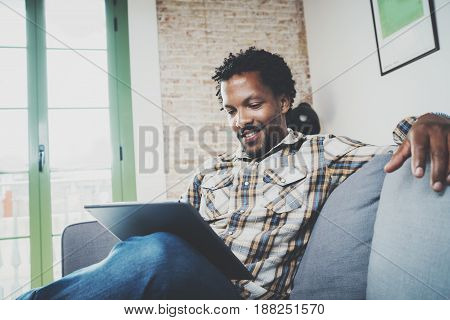Smiling African American man in headphone making video call via electronic touch pad while sitting on sofa at home.Concept of guy using Internet-enabled electronic device indoor.Blurred background