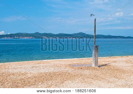 One metal shower on the pebble sandy beach on the background of a hill range with many small houses a line of buoys and azure blue sea. Blue cloudy sky. Zadar Croatia