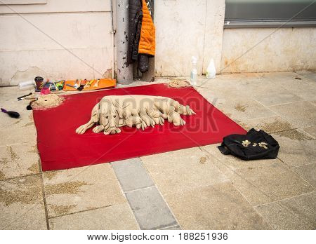 Regensburg,Germany-May 20,2017:A dog and her litter made out of sand lie in display in a street