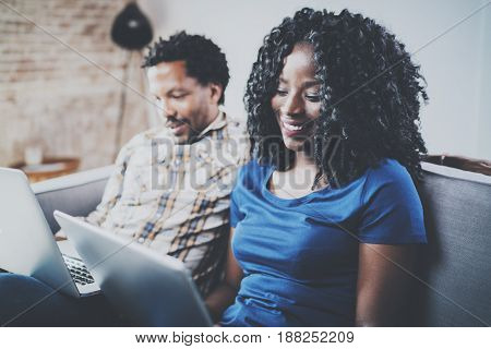 Closeup view of Happy african american couple relaxing together on the sofa.Young black man and his girlfriend using laptop at home in the living room. Horizontal, blurred background