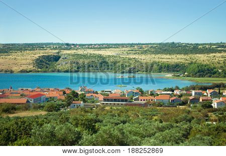 Crkva Sveti Duh church in Posedarje in Novigradsko More bay in blue azure water against the background of a hill green trees and houses with red roofs. Warm cloudless day in Croatia