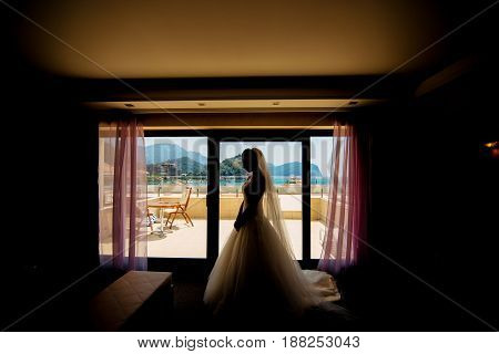 Silhouette of a bride in a wedding dress on a window in a hotel. The city of Petrovac, Montenegro.