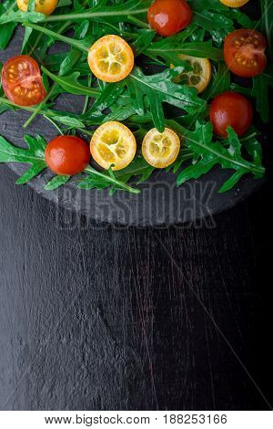 Arugula salad with kumquat and tomato cherry on slate plate. Top view. Healthy food. Diet