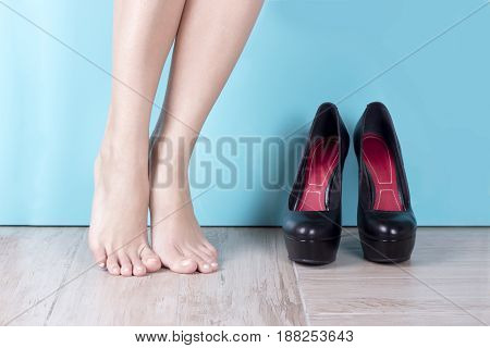 Bare legged women near high heel shoes. Exercise bare feet. Slim sporty legs. Woman's feet and shoes on a hardwood floor. A lot of space for text.