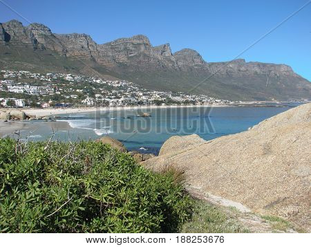 FROM CAMPS BAY, CAPE TOWN SOUTH AFRICA, HUGE BOULDER AND VEGETATION IN THE FORE GROUND AND A MOUNTAIN IN THE BACK GROUND