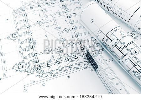 Architects Workspace With Project Plans, Rolled Blueprints And Folding Ruler