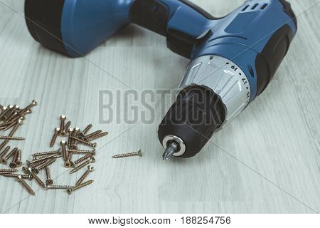 Cordless screwdriver or drill and screws on wooden background.