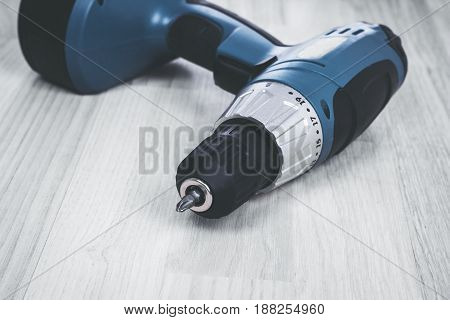 Cordless Battery screwdriver or drill isolated over wooden background.