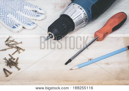 Carpenter screwing the crew with cordless screwdriver into wooden board.
