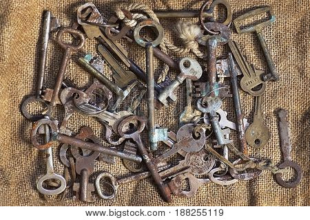 Different keys pile rusty old on burlap background