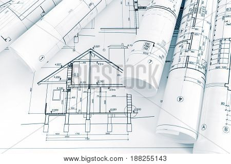 Architectural Project Of New House And Rolled Blueprints On Architect Workspace