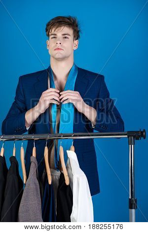 man with shaved face at wardrobe hanger with formal outfit and suit wearing jacket and tie on blue background