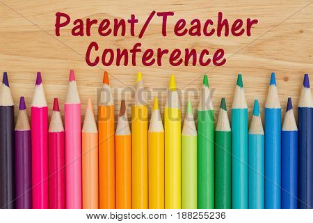 Parent Teacher Conference text with colorful pencil crayons on a desk