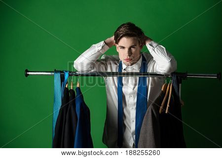 guy in the shirt and tie in closet with clothes on hanger on green background