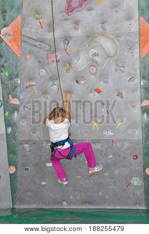 Infant girl in safety harness learning rock climbing doing first steps on vertical wall.