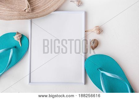 Frame mockup elegant female straw hat blue slippers sea shells on white background copyspace for text summer vacation clean minimalist styled image beach fashion flat lay top view