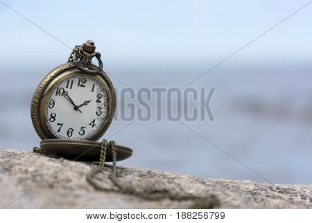 round pocket watch with chain on stone on background of sky with clouds dial hands