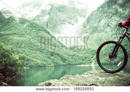 Mountain bike wheel and mountain lake landscape, Norway