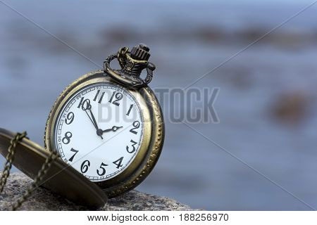 round pocket watch with chain on stone on background of the sky dial hands