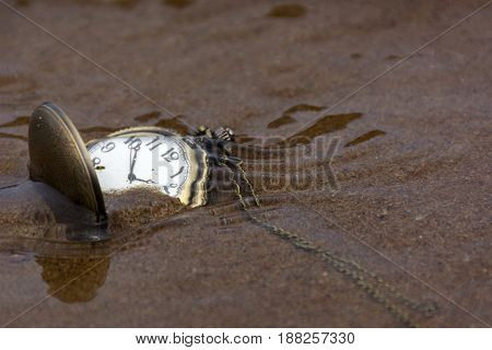 round pocket watch on the sand under the water