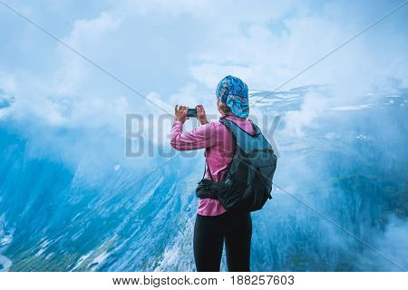 Nature photographer tourist with camera shoots while standing on top of the mountain. Beautiful Norway Nature