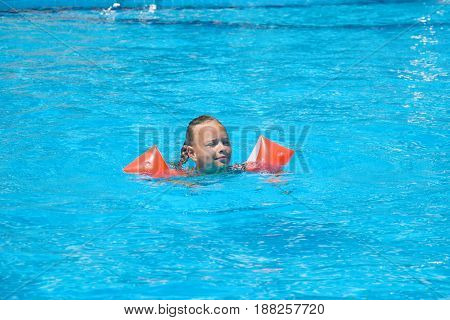Cute little girl learning how to swim in swimming pool outside.