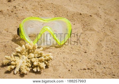 Swimming mask and a piece of yellow coral on a sandy beach. Sport and diving concept.