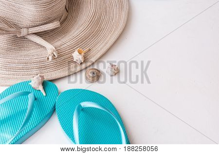 Elegant women's straw hat blue flip flops sea shells on white concrete background summer vacation fashion clean minimalist styled image top view