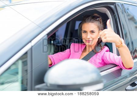 Close-up of a woman hand showing a thumbs-up sign out with car windows.