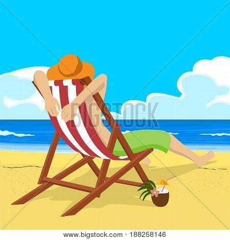 Young man in straw hat sitting in deck chair on the tropical beach looks into the distance