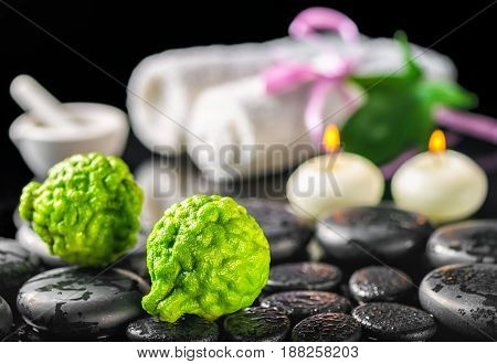 Spa Concept Of Bergamot Fruits, Leaf, Candles, Mortar, White Towels And Zen Basalt Stones With Water