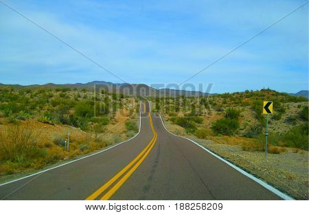 Empty winding road going through the desert landscape