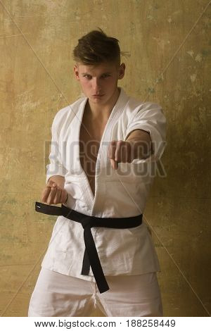 Strong Fit Athlete In White Kimono With Black Belt