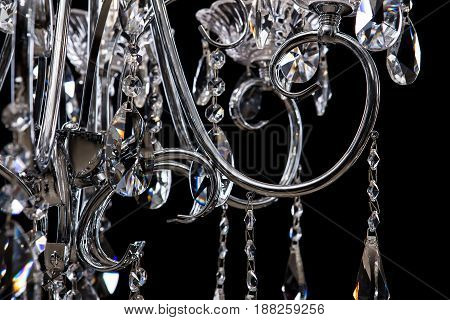 Chandelier for interior of the living room. Large silver crystal chandelier isolated on black background. Details close-up photo for designers.