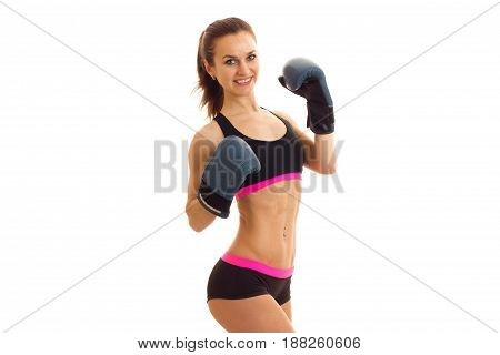 smiling attractive athletic girl smiles holding hands in boxing gloves is isolated on a white background